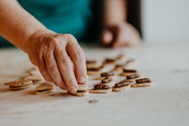 Aggiungere delicatamente un altro biscotto come per chiudere e immergere la parte superiore nella glassa al cioccolato.