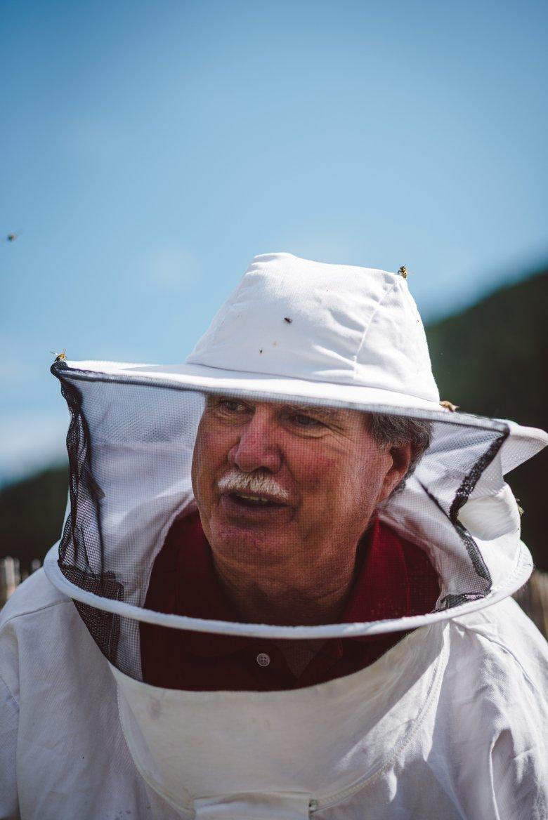 Reinhard Hetzenauer con un casco protettivo da apicoltore: suo nonno lo ha fatto appassionare all'apicoltura.