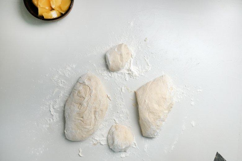 Mettere un bel po' di farina sulla superficie di lavoro, impastare con forza e tagliare dei dischetti nella misura di una piccolo piatto e farli lievitare nuovamente.